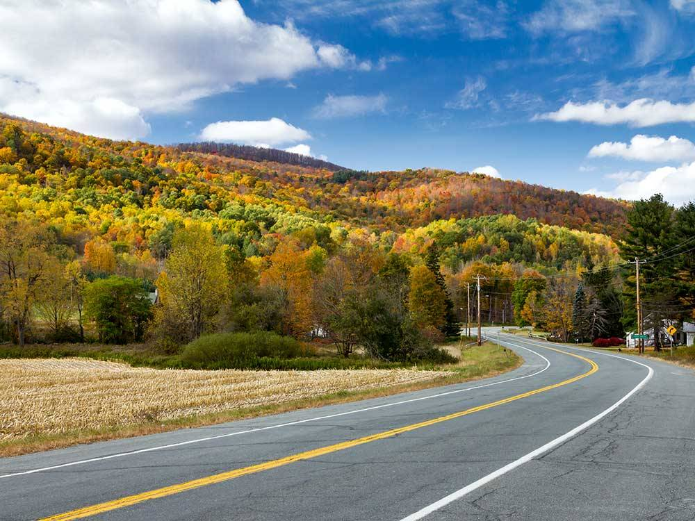 Highway with beautiful orange green and tan rolling hills at PINE LAKE RV RESORT  COTTAGES