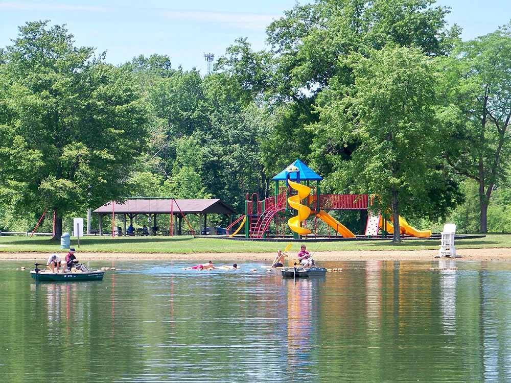 People swimming and boating on the lake with playground in the background at ROUNDUP LAKE CAMPGROUND