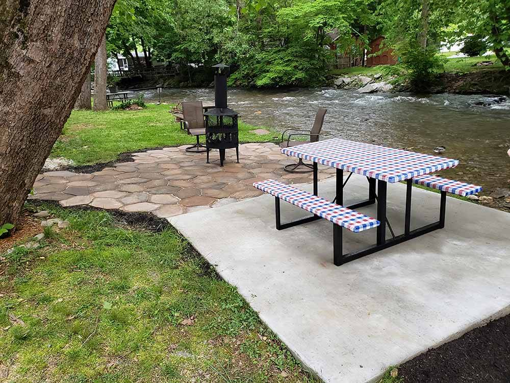 A picnic table by the river at STONEBRIDGE RV RESORT