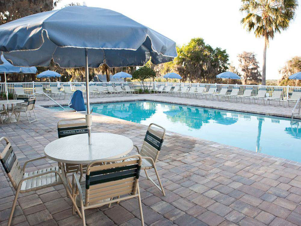 Swimming pool with outdoor seating at GRAND LAKE RV  GOLF RESORT