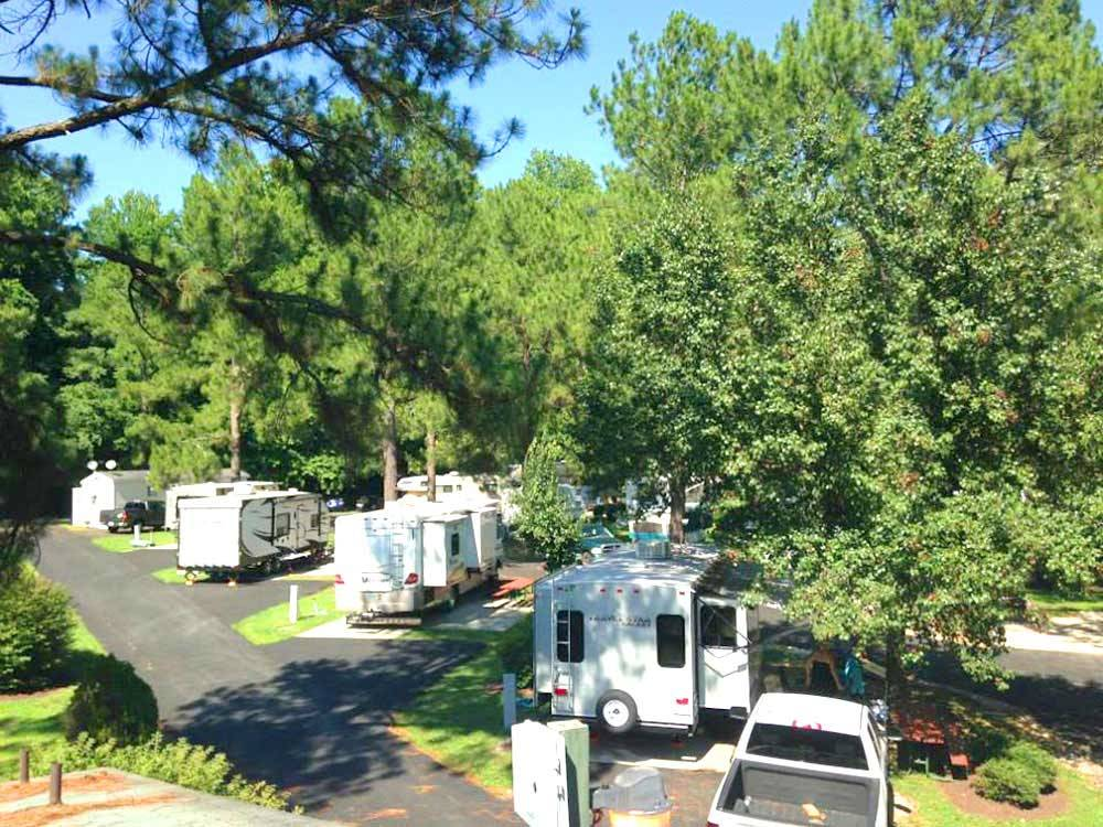 White travel trailers camping at campsite and green trees at AMERICAN HERITAGE RV PARK
