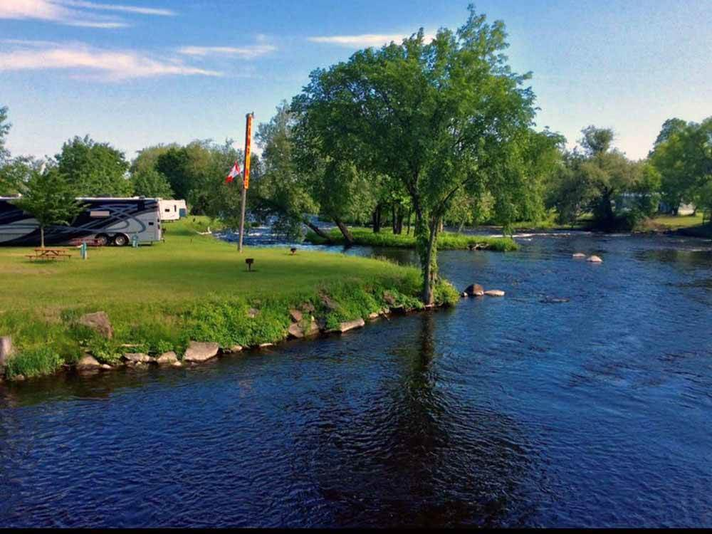 RV sites along the water at BABBLING BROOK RV PARK