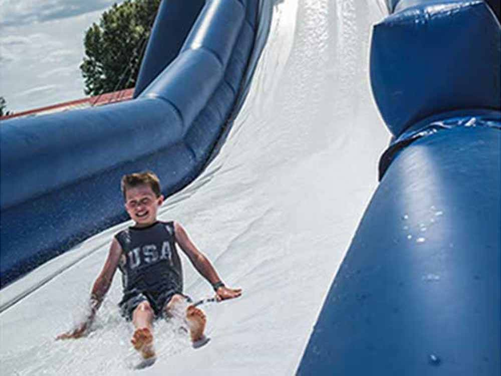 A boy sliding down an inflatable waterslide at CABOOSE LAKE CAMPGROUND