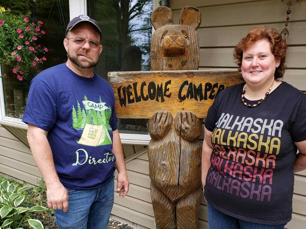 Couple next to a wooden bear holding a welcome sign at KALKASKA RV PARK  CAMPGROUND