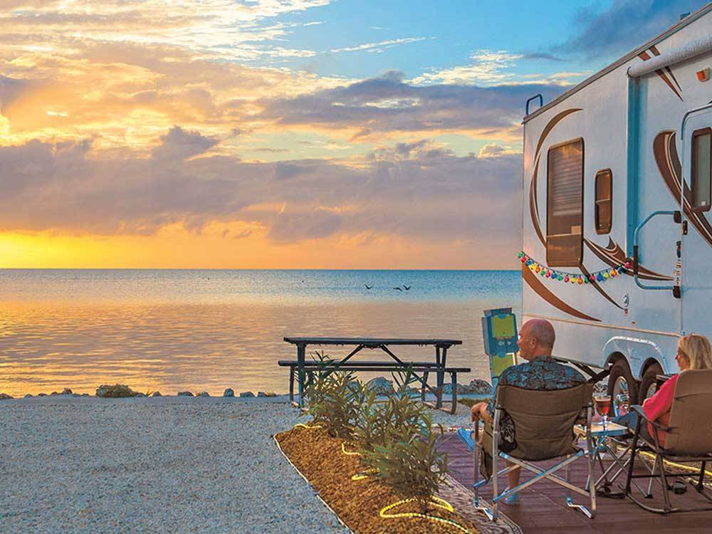 Couple sitting next to RV viewing the sunset at FIESTA KEY RV RESORT