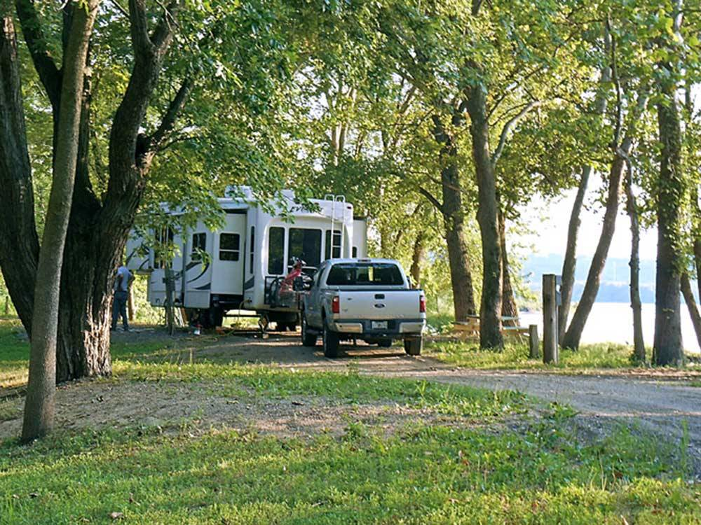 RV and truck in a treed site with lakeview at MILLPOINT RV PARK