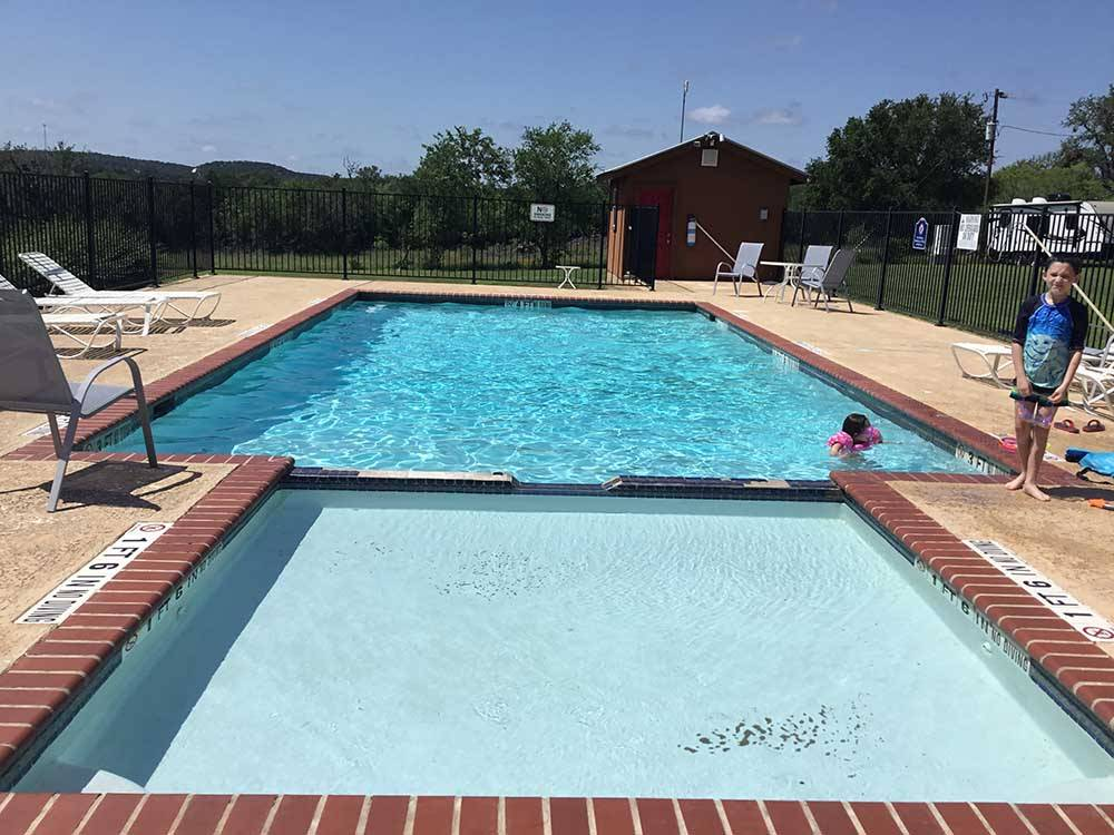 The pool area with a table and chairs at TRIPLE T RV RESORT