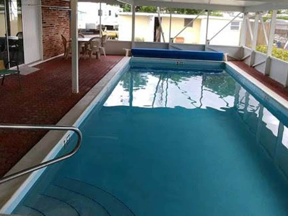 Calm indoor pool with red brick surface surrounding it at PALM BEACH TRAVELER RV PARK