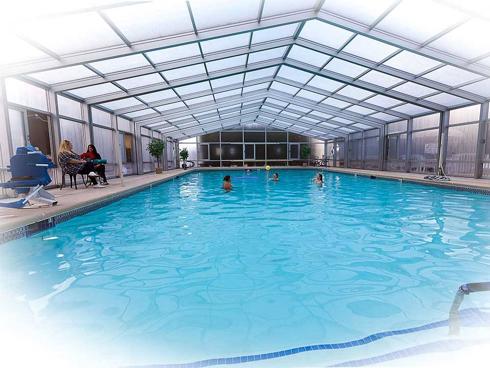People enjoying the indoor swimming pool at PREFERRED RV RESORT