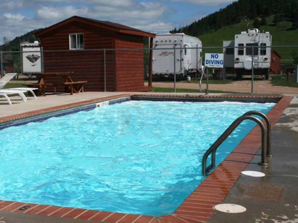 The pool with camp sites behind it at NO NAME CITY LUXURY CABINS  RV PARK