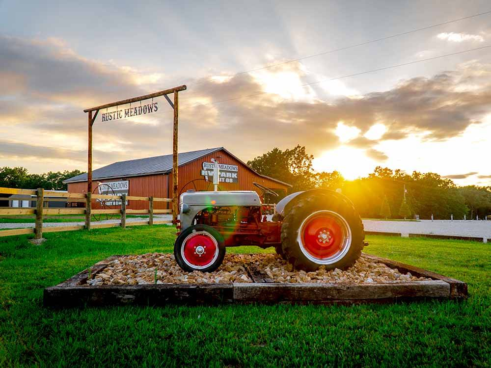 Antique tractor and barn at park entrance at RUSTIC MEADOWS RV PARK
