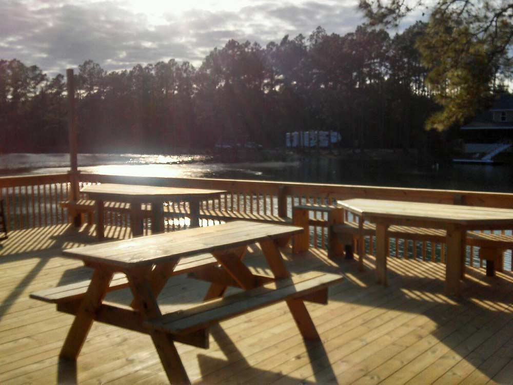 Wooden picnic tables alongside glassy lake with sun reflecting off of it at MCINTOSH LAKE RV PARK