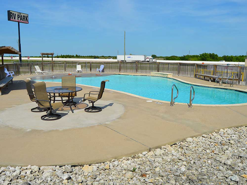 Swimming pool with outdoor seating at I 35 RV PARK  RESORT