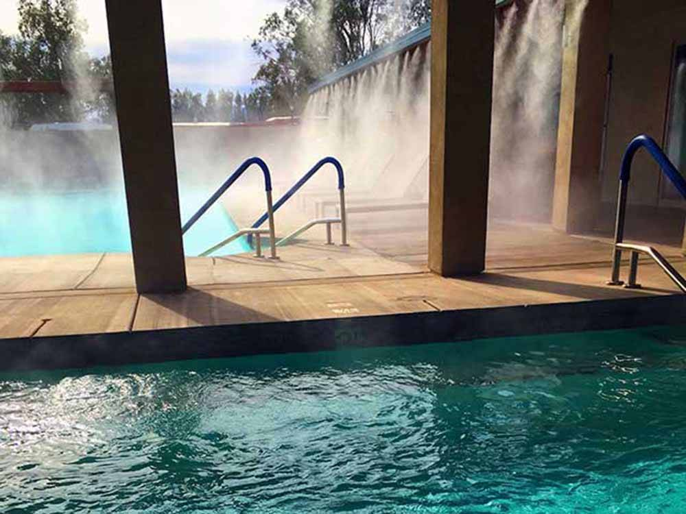 Misters spraying lounge chairs along clean community pool at CATALINA SPA AND RV RESORT