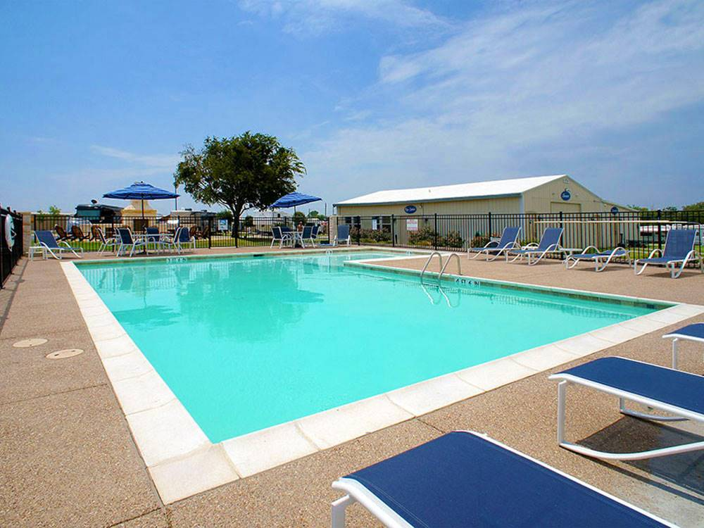 Large swimming pool with blue lounge chairs at SHADY CREEK RV PARK AND STORAGE