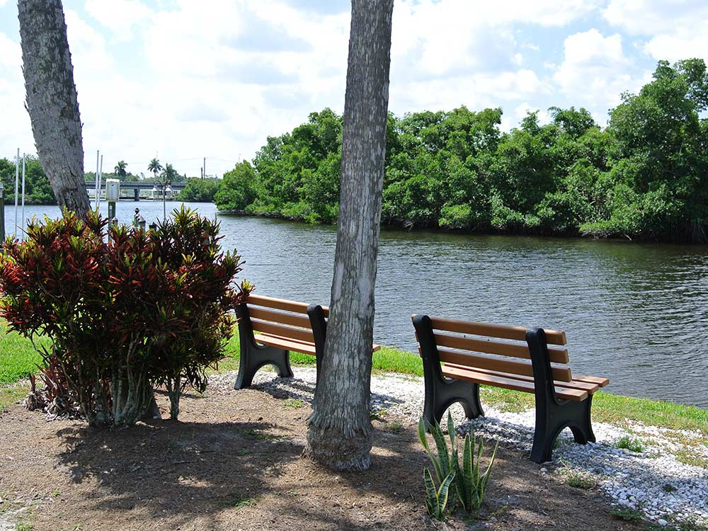 Wooden benches looking out onto flowing river at ORANGE HARBOR CO-OP  RV RESORT