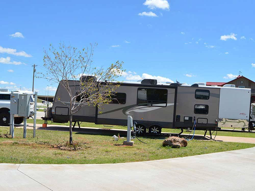 Trailer camping at campsite with paved road at MUSTANG RUN RV PARK