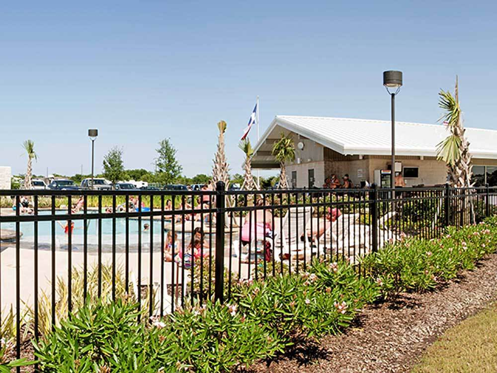 Swimming pool  grassy area  at MONT BELVIEU RV RESORT