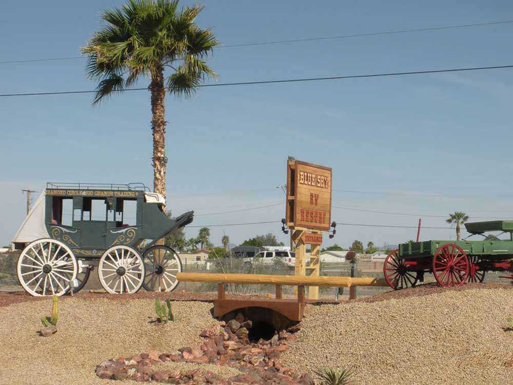 Stagecoach and wagon with park sign at BLUE SKY RV RESORT