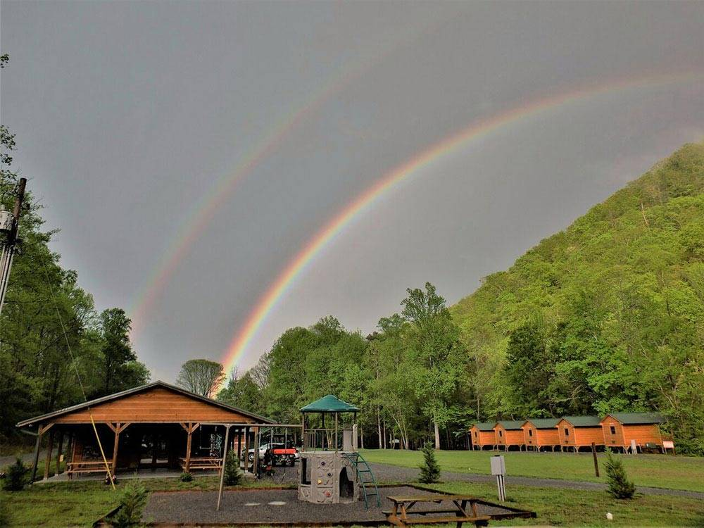 Double rainbow in background of wooden cabin and playground at PIGEON RIVER CAMPGROUND