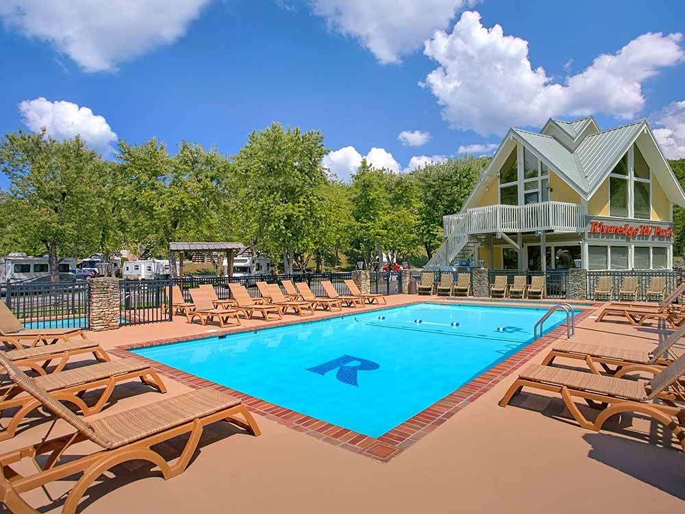 Adult and kids pool with chaise lounges at RIVEREDGE RV PARK  CABIN RENTALS