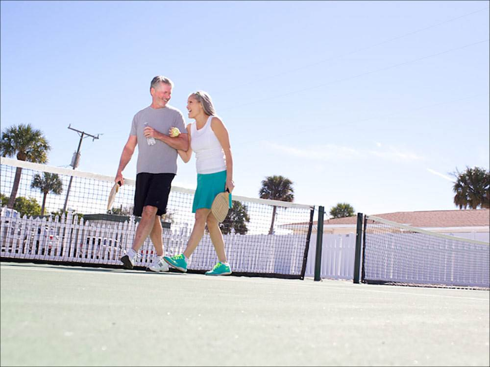 Couple playing tennis at OCEAN BREEZE RESORT