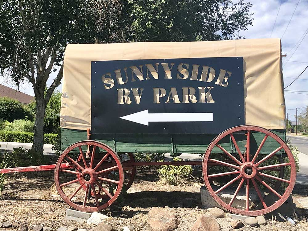 Covered wagon with park sign at SUNNYSIDE RV PARK