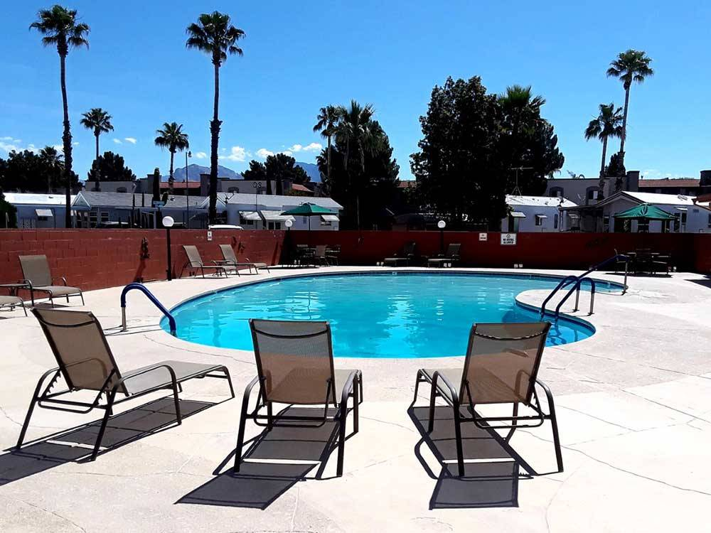 Swimming pool with chaise lounges at SOUTH FORTY RV RANCH