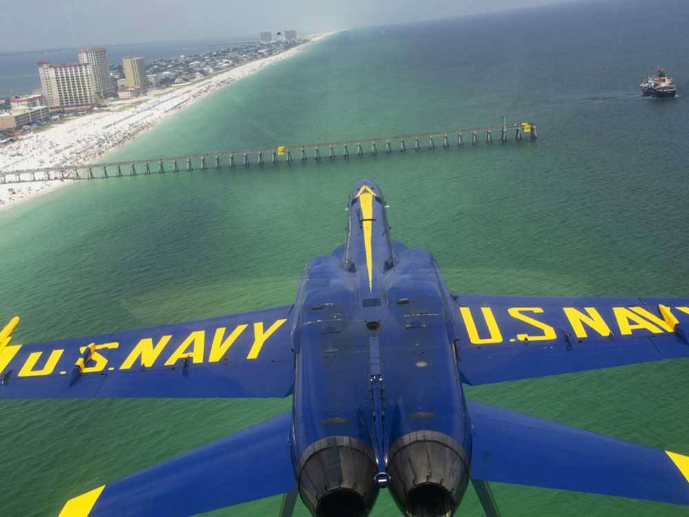 Blue US Navy plane flying over ocean at AHOY RV RESORT