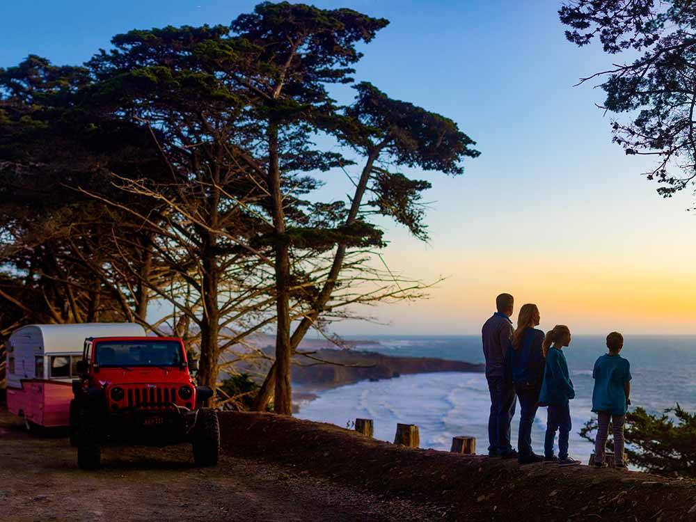 A family looking out at the ocean at sunset at VISIT SLO CAL - SAN LUIS OBISPO COUNTY