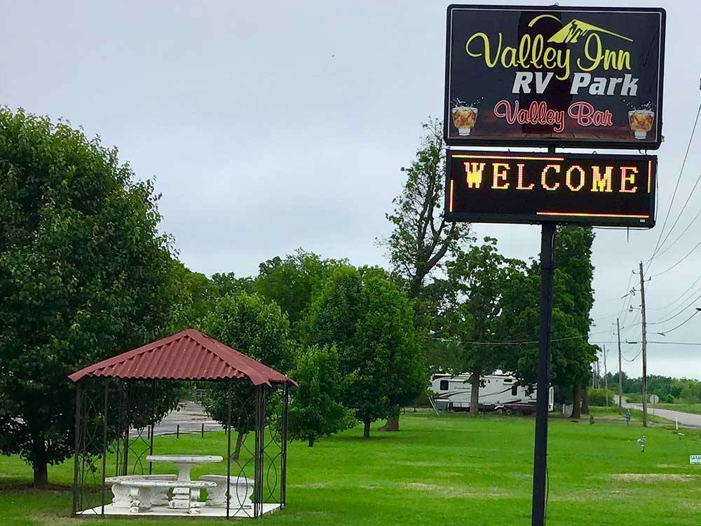 Sign at park entrance with covered seating area at VALLEY INN RV PARK
