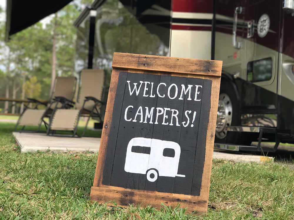A Welcome Campers sign sitting in front of a Class A motorhome at LANDING RESORT