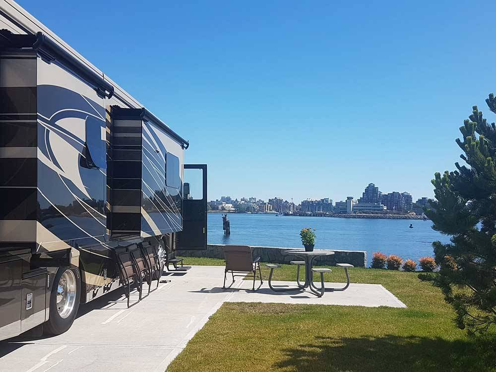 Large RV parked alongside table overlooking large body of water at SALISH SEASIDE RV HAVEN
