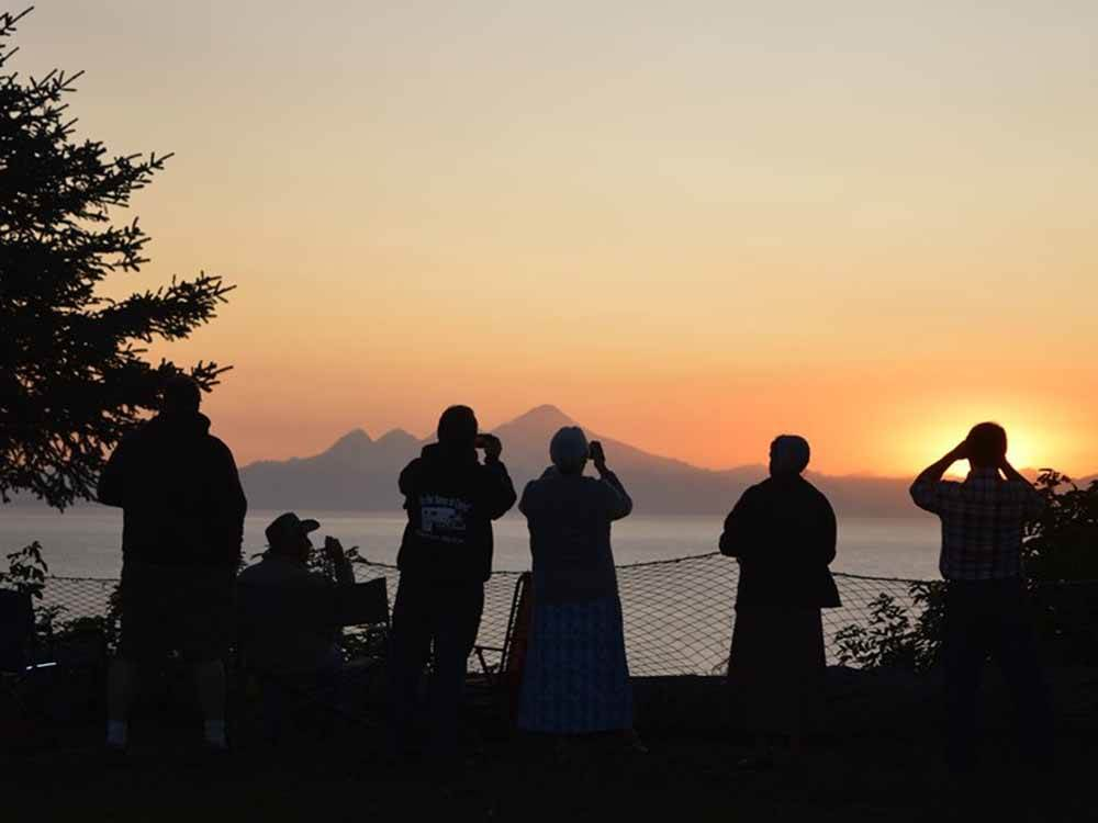 Silhouette of people looking at a sunset over water at WHISKEY POINT CABINS AND RV PARK