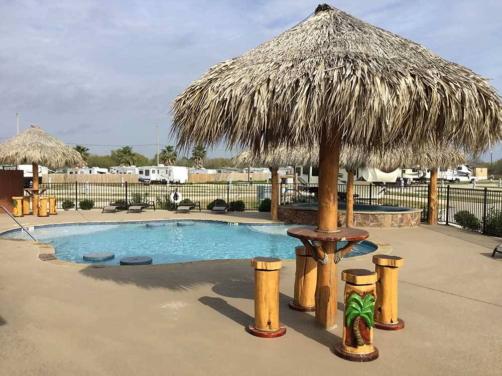 Swimming pool and palm leaf umbrellas at SUMMER BREEZE USA KEMAH