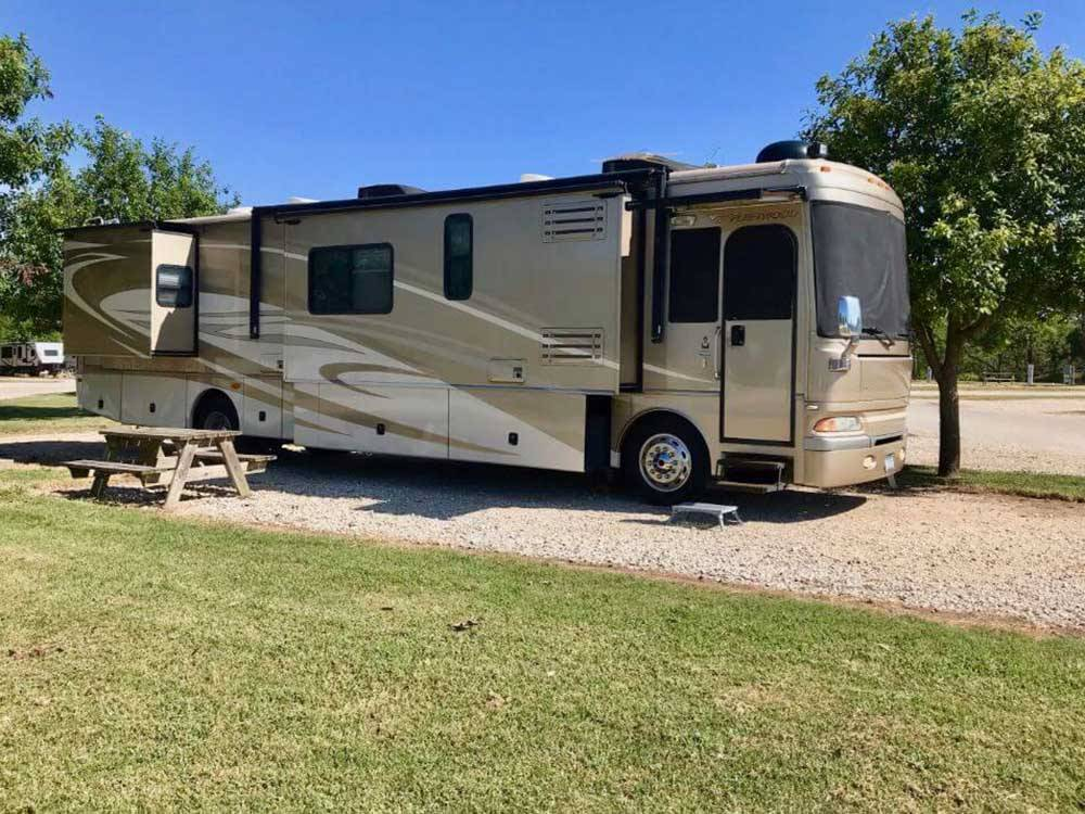 A class A motorhome parked in a gravel RV site at TEXAS FREEDOM RV VILLAGE
