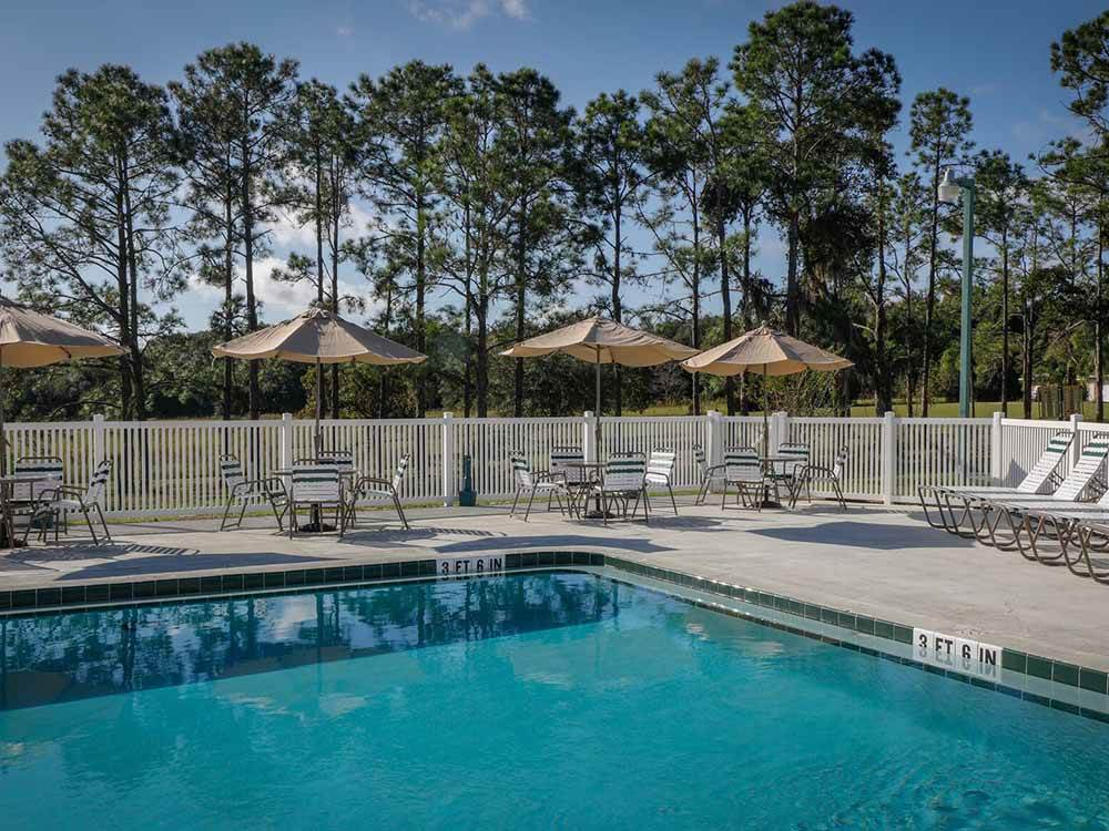 The pool area with lounge chairs and tables with umbrellas at RIDGECREST RV RESORT