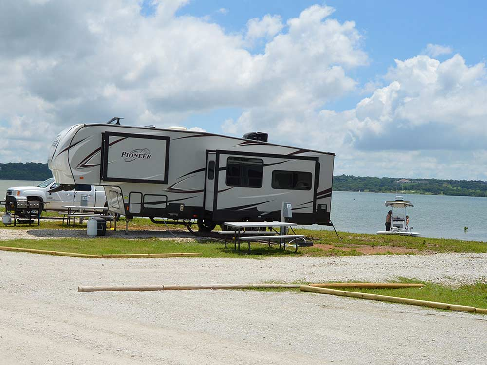 Large trailer with pop out extended parked along lake with boat and truck in background at LAKE WACO RV PARK  MARINA