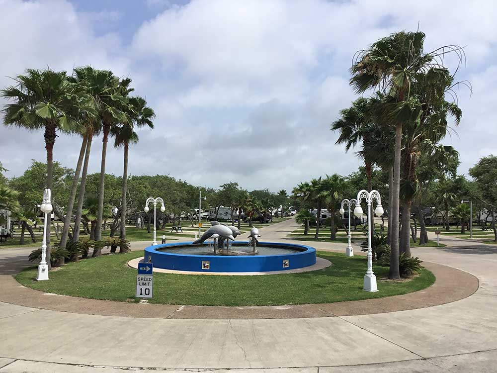 Circular fountain with dolphin sculptures at LAGOONS RV RESORT