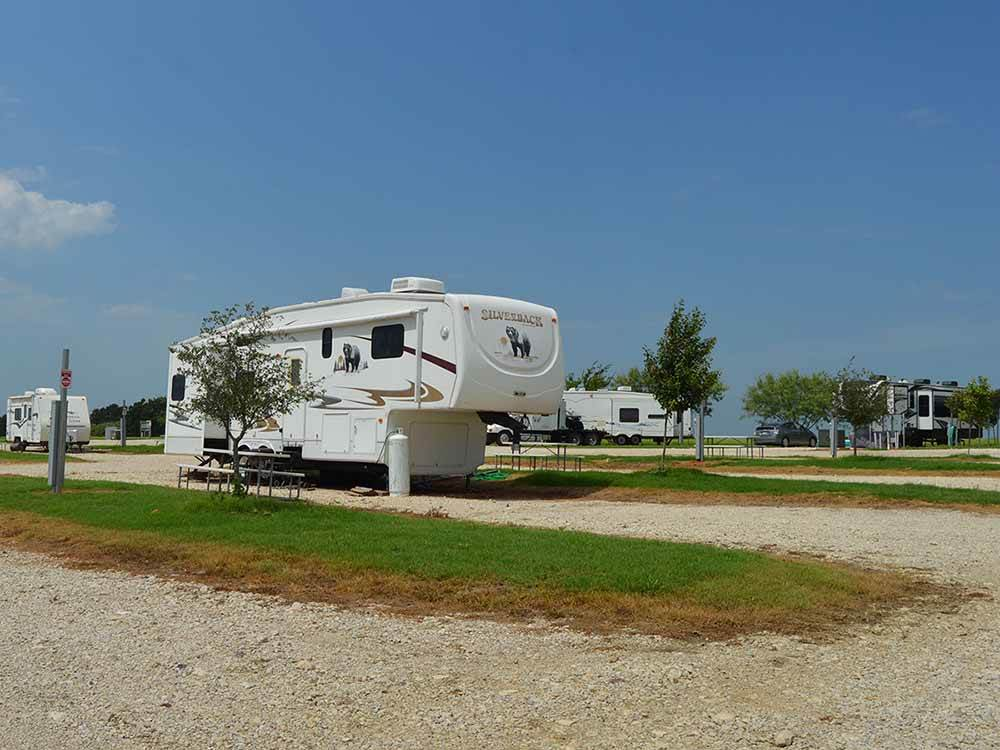A fifth-wheel RV parked in a gravel RV site at SHARK TOOTH RV RANCH