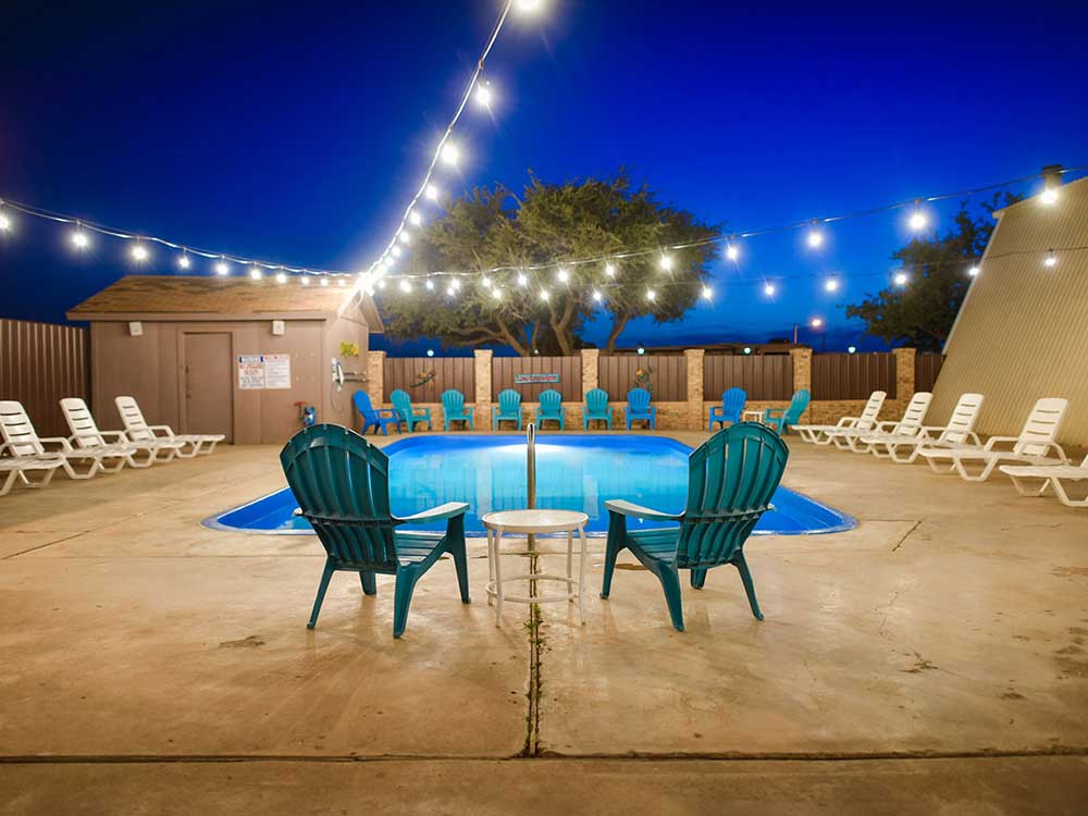Blue and white lounge chairs around the swimming pool under lights at OPDYKE WEST RV PARK