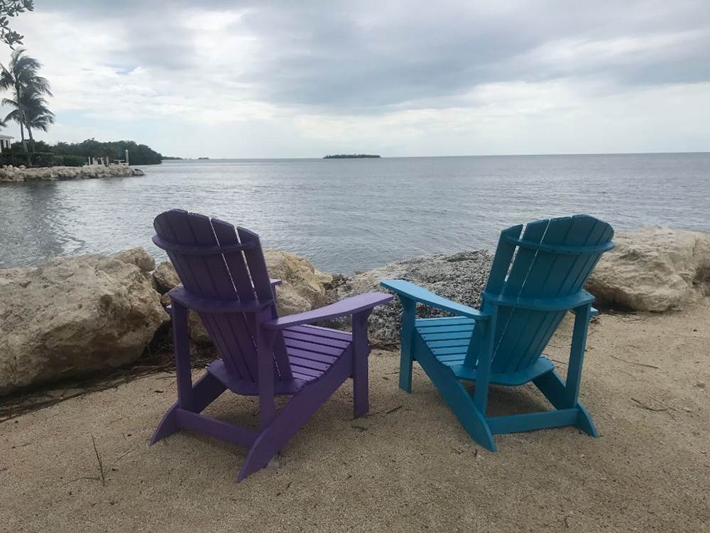 Two colorful lounge chairs near the beach at COCONUT CAY RV PARK  MARINA