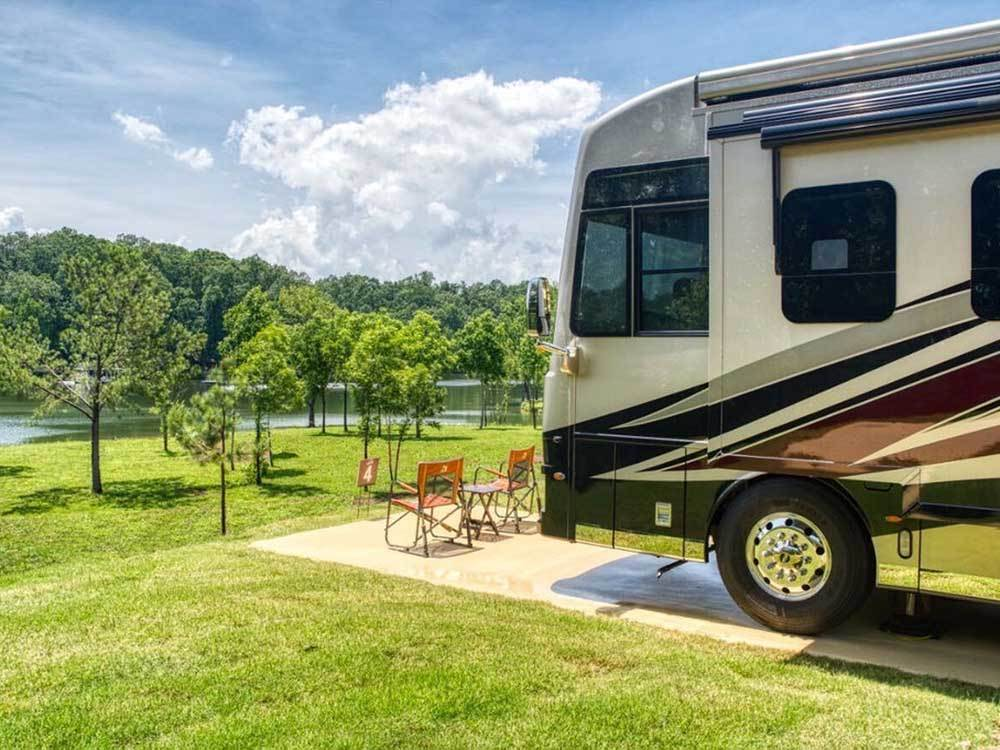 A motorhome in a paved RV site overlooking the water at TWIN CREEKS RV RESORT