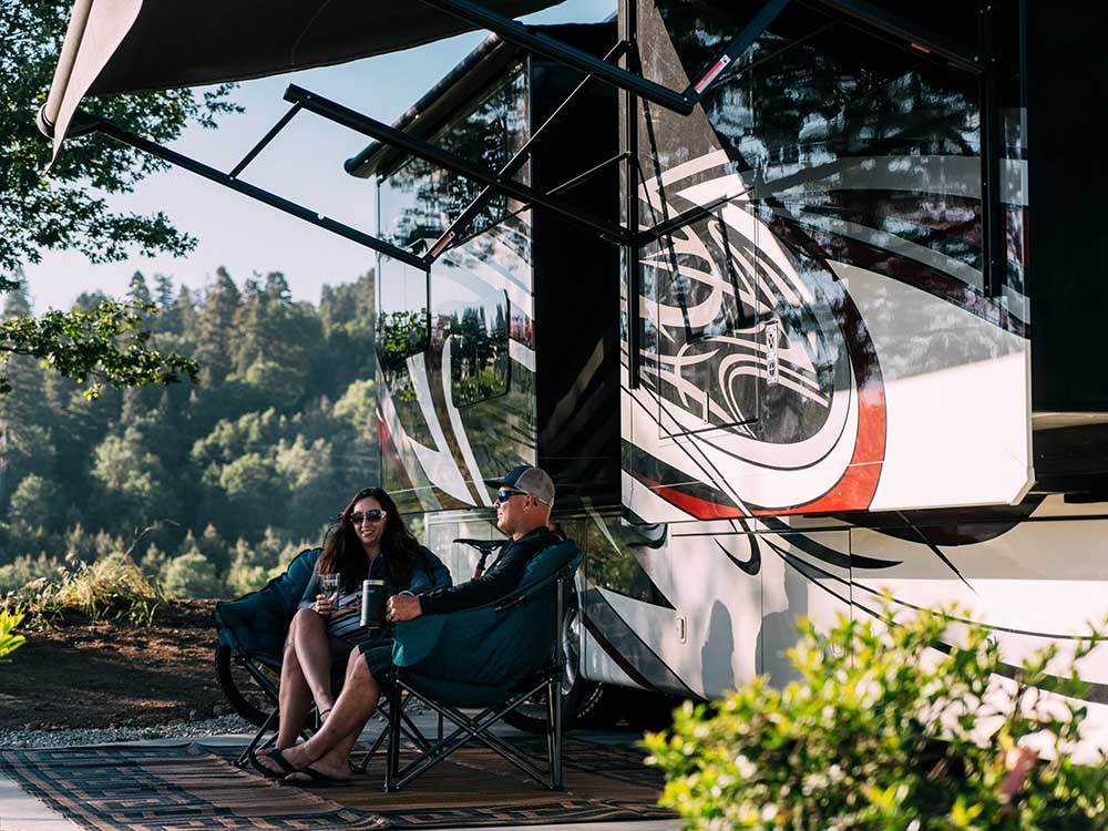 A couple sitting outside of their RV at SKYPARK CAMP  RV RESORT