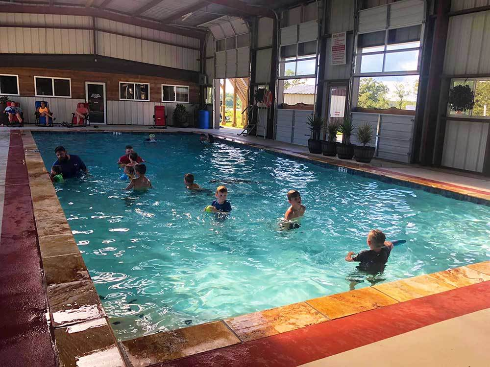Kids playing in the indoor swimming pool at CAMP LANGSTON RV RESORT