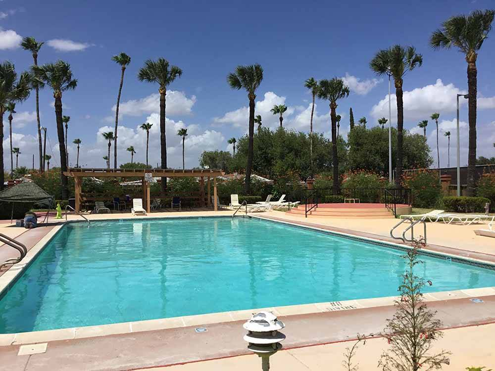 A view of the pool surrounded by palm trees at TIP O TEXAS RV RESORT