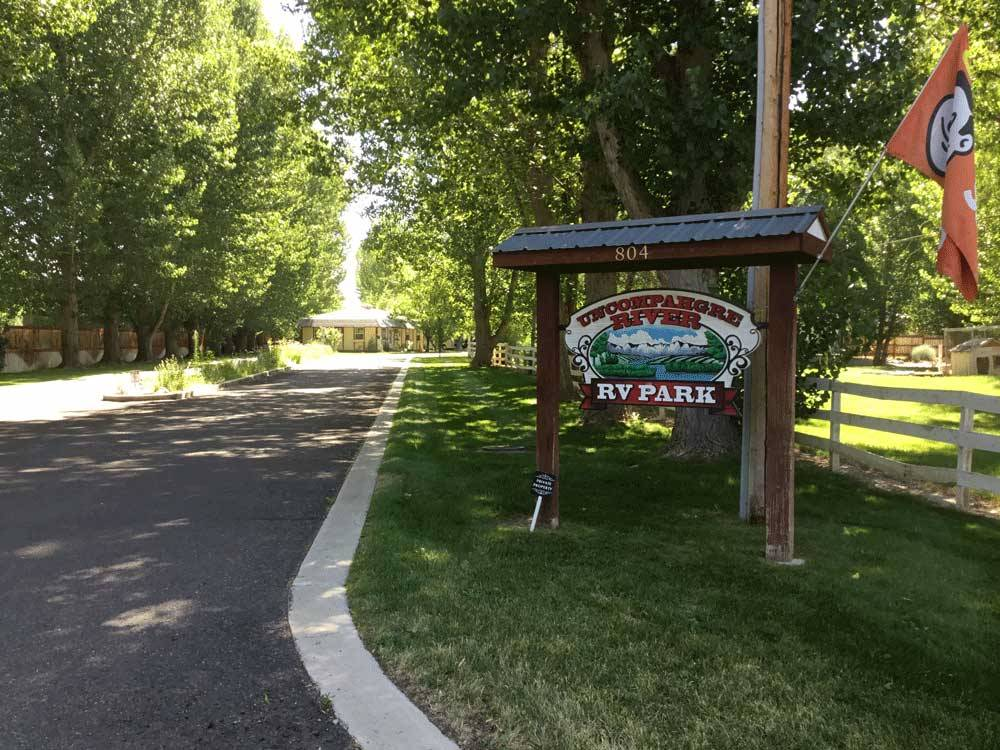 Sign at the tree lined park entrance at UNCOMPAHGRE RIVER ADULT RV PARK