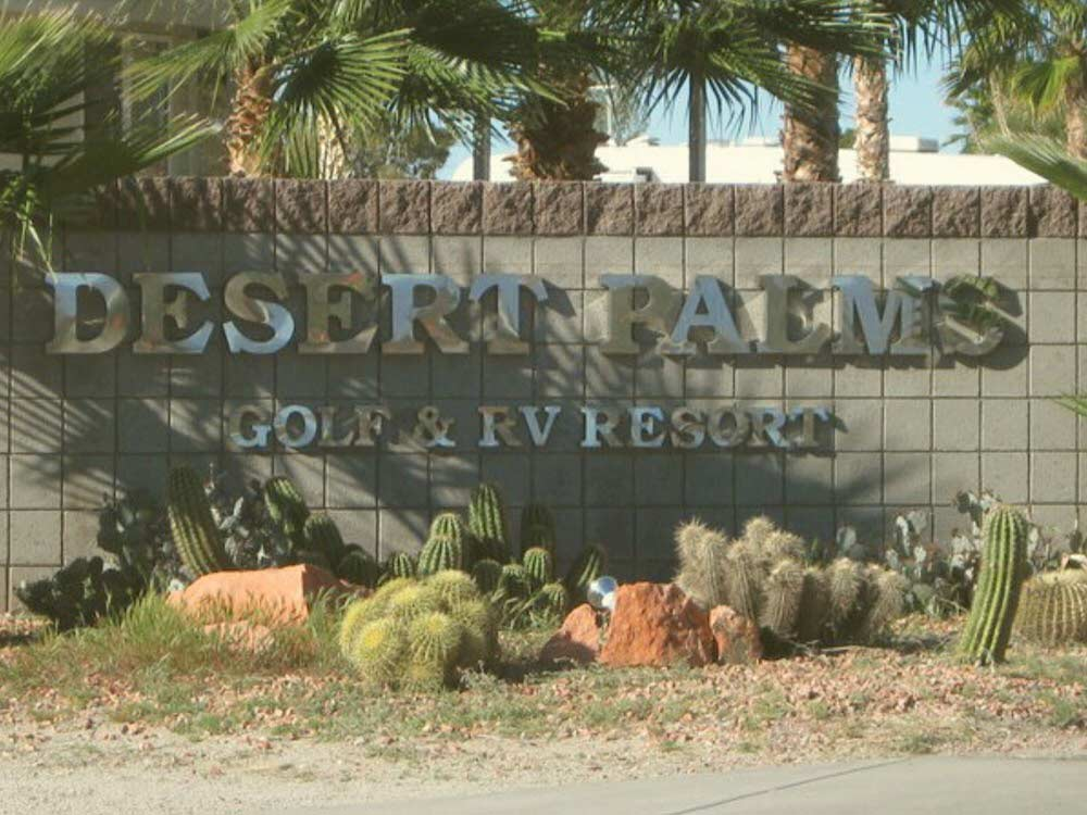 Chrome text on brick wall of front entrance sign at DESERT PALMS RV RESORT