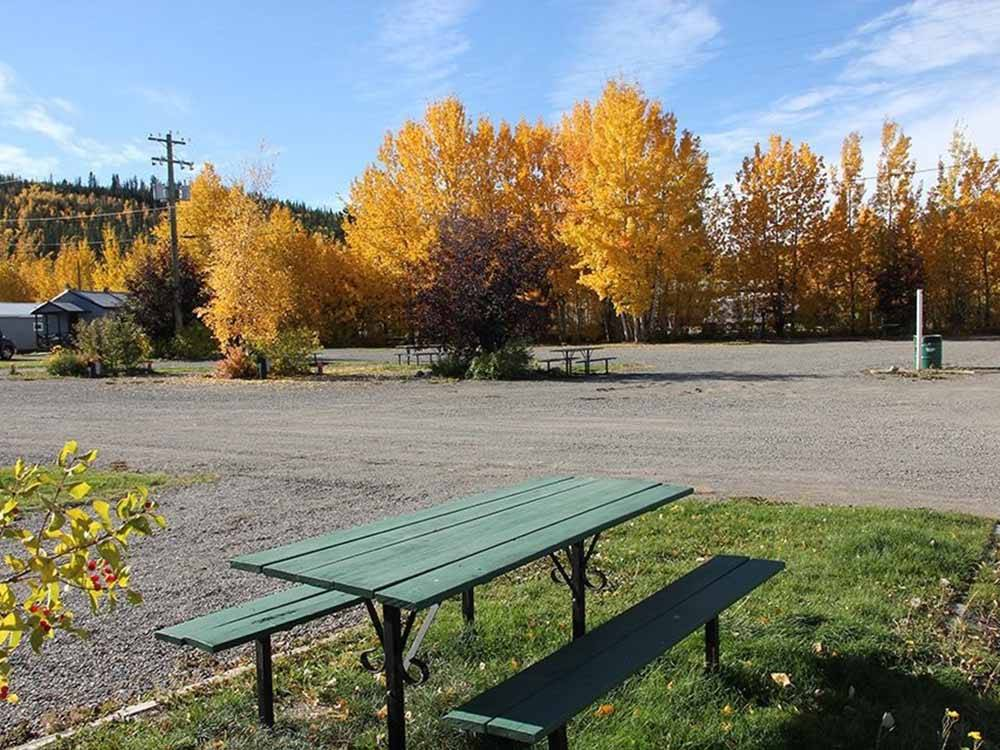 A green picnic bench at one of the RV sites at CARMACKS HOTEL  RV PARK