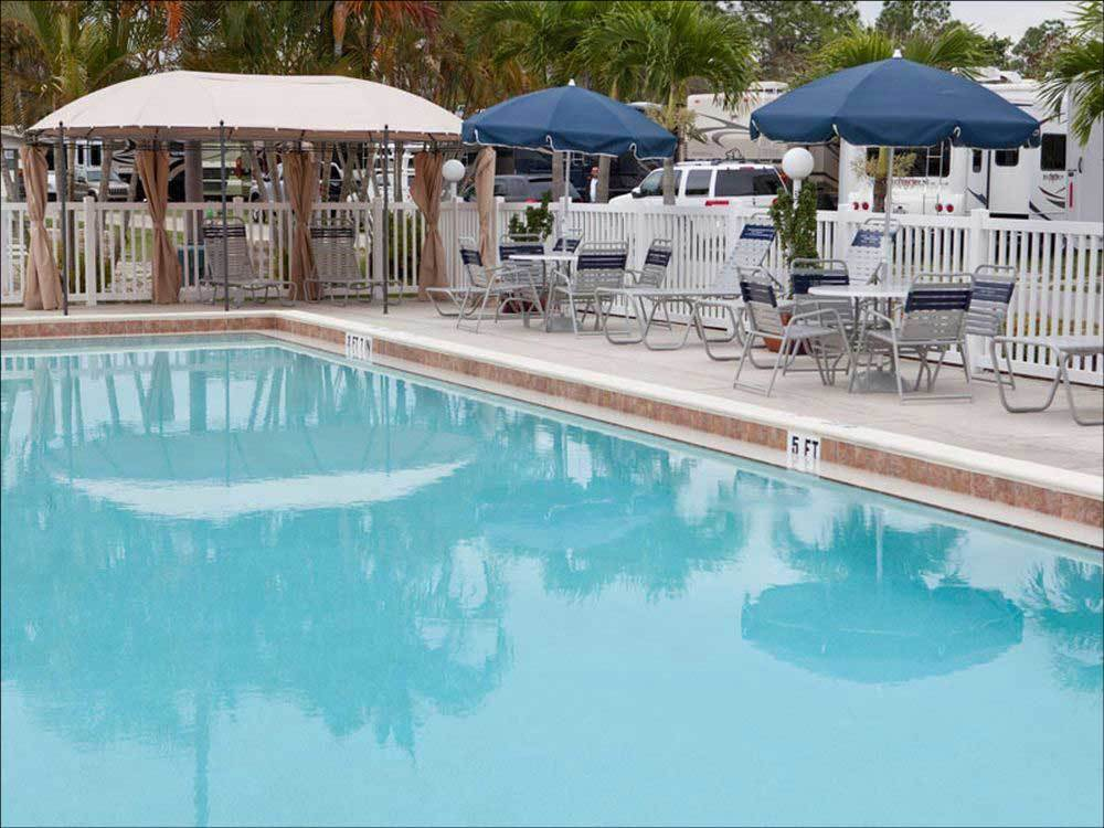 Swimming pool with outdoor seating at CLUB NAPLES RV RESORT